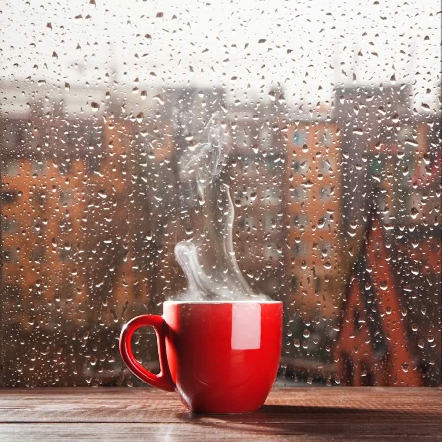 taza de cafe caliente delante de una ventana de lluvia